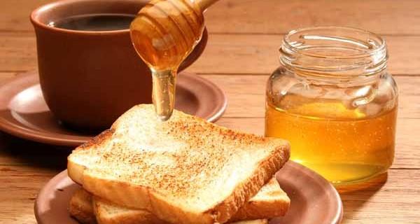Breakfast scene. Honey pouring over toast bread